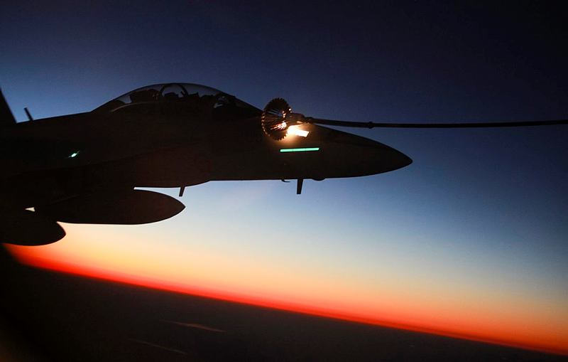 A Royal Australian Air Force (RAAF) F/A-18F Super Hornet aircraft refuels from a RAAF KC-30A Multi-Role Tanker Transport aircraft as the sun sets over Iraq.