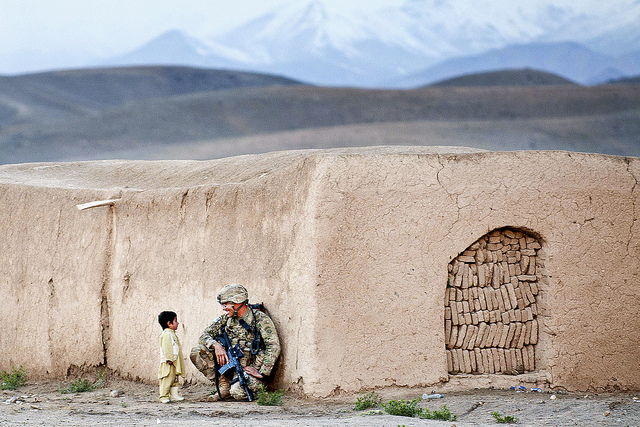 Sgt. Joshua Smith, a paratrooper with the 82nd Airborne Division's 1st Brigade Combat Team, chats with an Afghan boy during an Afghan-led clearing operation April 28, 2012, Ghazni province, Afghanistan. The soldier studied the Pashtun language prior to his deployment to southern Ghazni. (U.S. Army photo by Sgt. Michael J. MacLeod)