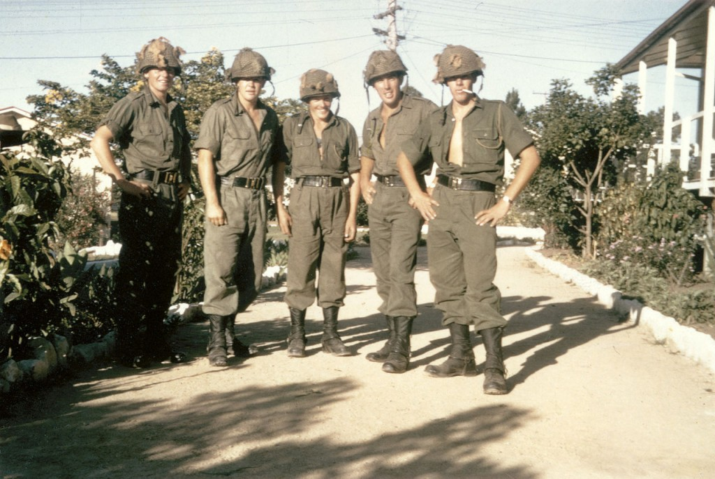 Members of 8 platoon, C Company, 6th Battalion, Royal Australian Regiment (6RAR), in the battalion lines at Enoggera, Queensland, prior to deployment to Vietnam in May 1966. From left: 2781803 Private (Pte) Rodney Cox of Ganmain, NSW; 2781794 Pte Gordon Stafford of Gunnedah, NSW; 2781823 Pte Neil (Pop) Baker of Newcastle, NSW; 2781790 Pte Mark (Scrub) Minell of Moree, NSW; 2781809 Pte Graham Irvine of Coolamon, NSW. All five men were called up in the first intake of national service in July 1965. Note the protective steel helmets with camouflage netting, usually worn by Australian infantry on operations in areas known to have been mined by the enemy.