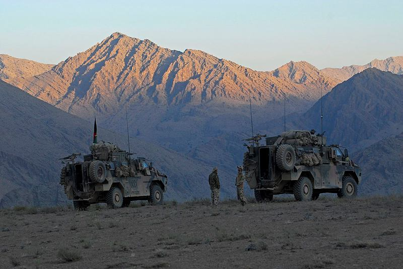 Special Operations Task Group Bushmaster vehicles take up an overwatch position as troops prepare to clear the valley below.