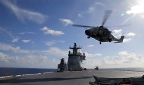 A MRH-90 Taipan helicopter, conducts a vertical replenishment during First of Class Trials, onboard HMAS Canberra.