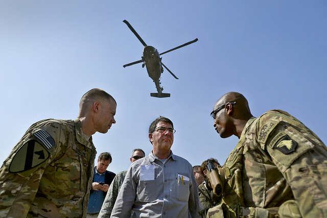 As a Black Hawk helicopter rumbles overhead, Deputy Secretary of Defense Ashton B. Carter speaks with Brig. Gen. Ron Lewis, right, during a visit to bases in Afghanistan