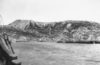 Gallipoli Peninsula, Turkey. Summer 1915. A view from the sea of Anzac Cove. On the left is Ari Burnu, left background is Plugge's Plateau, to the right is MacLagan's Ridge with Anzac Gully between. New Zealand and A Division Headquarters (half-way up hill) are under Plugge's Plateau on the left. This is the left hand image in a two part panorama.