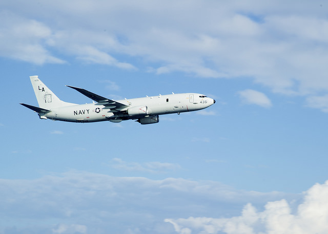 "PHILIPPINE SEA (Sept. 26, 2014) A P-8A Poseidon, assigned to the ""Mad Foxes"" of Patrol Squadron (VP) Five from Okinawa, Japan, conducts a fly-by near amphibious assault ship USS Peleliu (LHA 5)."