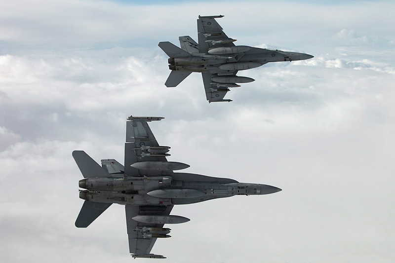 A RAAF F/A-18A Hornet (foreground) and a RAAF F/A-18F Super Hornet (rear) bank away from a RAAF KC-30A tanker aircraft during a mission in the Middle East Region for Operation OKRA. During the mission the recently arrived F/A-18 Hornets flew alongside of F/A-18F Super Hornets that would soon return to Australia.