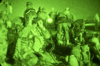An Afghan Soldier with 3rd Commando Kandak makes adjustments to his mounted night vision device while fellow Commandos and U.S. Soldiers with Special Operations Task Force - South conduct final mission preparation before conducting an operation to remove insurgents from Lam village, Khakrez District, Nov. 14, 2010, Kandahar Province, Afghanistan. (U.S. Army photo by Spc. Daniel P. Shook/Special Operations Task Force - South)(Released)