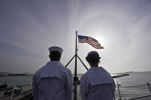 SINGAPORE (Jan. 30, 2012) Airman Joseph White, left, and Aviation Boatswain's Mate (Handling) Airman Kelsey Lefler stand by to lower the ensign as the Nimitz-class aircraft carrier USS John C. Stennis (CVN 74) departs Singapore. J