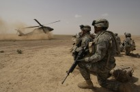 U.S. Army soldiers assigned to the 1st Brigade, 1st Armored Division wait to board a UH-60 Black Hawk helicopter during an air assault mission in the Al Jazeera Desert, Iraq, on March 22, 2006.