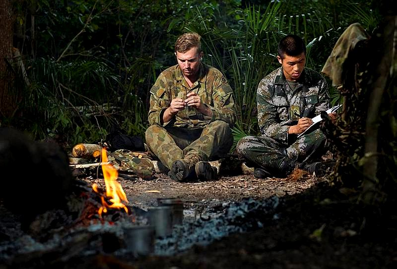 Australian Army officer Lieutenant Lachlan Joseph (left) makes a fishing lure, while People's Liberation Army of China officer Lieutenant Huang Jin Long updates his journal during the survival phase of Exercise Kowari 2014 in remote Northern Territory bushland.