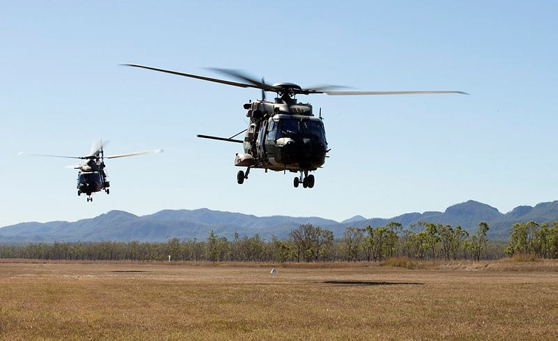 Australian Army MRH-90 Taipan multi-role helicopters depart an airfield at the beginning of a mission in Shoalwater Bay training area, near Rockhampton, Queensland, during Exercise Blue Dog 2.
