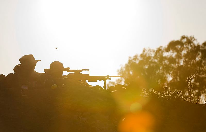 Australian Army recruits from Alpha Company, 1st Recruit Training Battalion, return fire on an enemy position during recruit training at Army Recruit Training Centre, Kapooka, New South Wales, in June 2015.