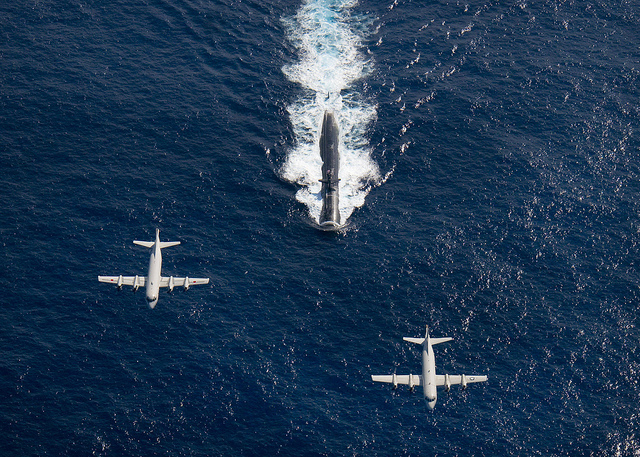 Two P-3 Orion anti-submarine and maritime surveillance aircraft from the Japan Maritime Defense Force, left, and the U.S. Navy, right, fly over the Los Angeles-class attack submarine USS Houston