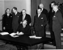 John Foster Dulles is shown signing the Tripartite Security Treaty