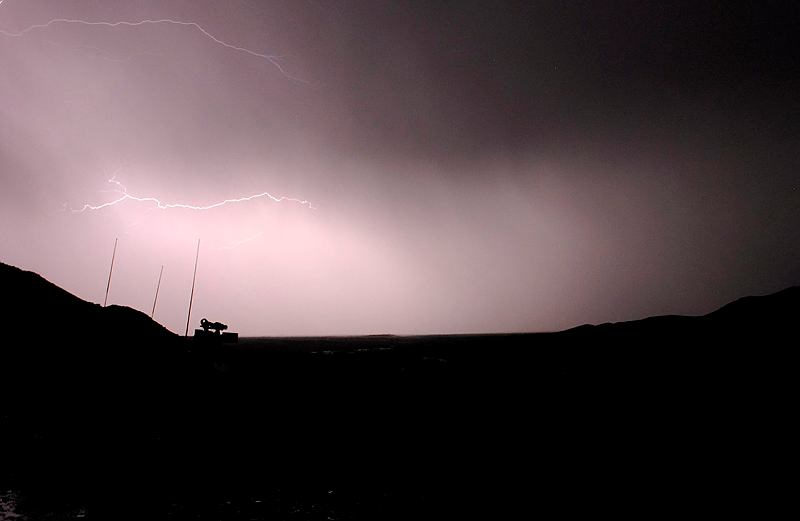 An Afghan summer storm breaks over a 1st Mentoring and Reconstruction Task Force Bushmaster Protected Mobility Vehicle during operations in the Baluchi Valley, southern Afghanistan