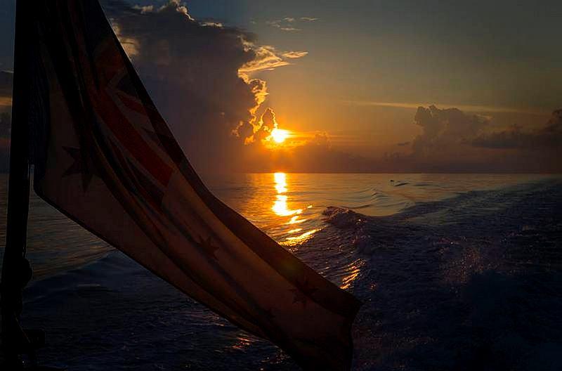 The Australian White Ensign flying from HMAS Larrakia's quarterdeck at sunset in the South China Sea.