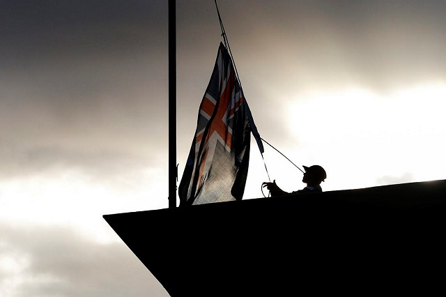 The Australian National Flag is brought down onboard HMAS Sydney as they depart Eden after de-ammunitioning for the last time.