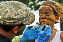 A Soldier transforms 7-year-old Kayiah into a camouflaged Army Ranger at the 6th Ranger Training Battalion's annual open house on Eglin Air Force Base, Fla., May 12, 2012.
