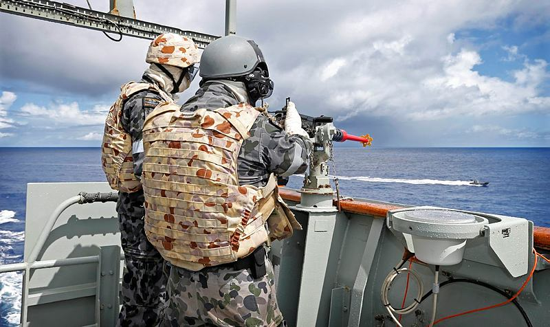 "Able Seaman Boatswains Mate Rory Dow (right) takes aim on a ""hostile"" target with the 12.7 mm gun during a damage control exercise onboard HMAS Success while in transit to the Middle East as part of Operation MANITOU."