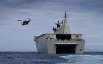 A MRH 90 helicopter takes off from HMAS Canberra's flight deck while the ship is docked down and conducting landing craft operations.
