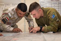 Task Group Taji Australian Army trainer Corporal Jeffrey Cummings confirms with a regular Iraqi Army soldier how to accurately mark and gauge distances during a navigation lesson at the Taji Military Complex in Iraq.