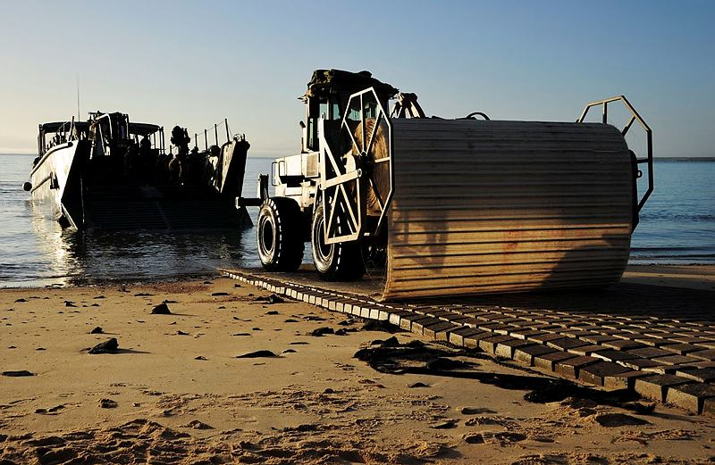 An Australian Army vehicle lays a protective mat over the beach at Sabina Point prior to other vehicles coming ashore from HMAS Choules in Shoalwater Bay, Queensland, as part of Exercise Talisman Saber 2013.