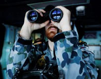 Maritime Warfare Officer, Sub Lieutenant Officer Samuel Archibald searches using binoculars on the bridge of HMAS Perth in the search for missing Malaysian Airlines Flight MH370 as part of OPERATION SOUTHERN INDIAN OCEAN.