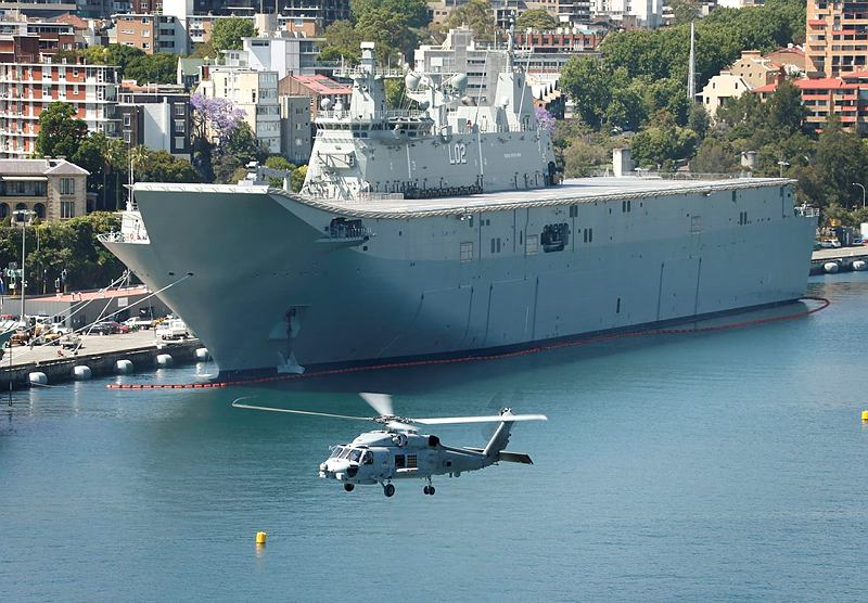 The Royal Australian Navy's latest helicopter, the MH60R 'Romeo' Seahawk, flies past the Navy's latest ship, NUSHIP Canberra in Sydney, NSW.
