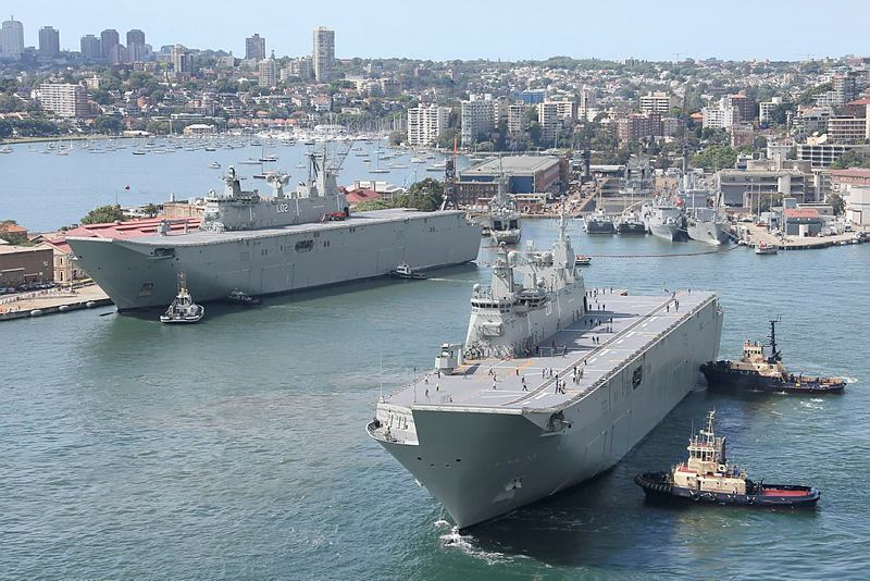 NUSHIP Adelaide is manoeuvred towards her berth at Fleet base East - Garden Island while her sister ship, HMAS Canberra, can be seen near the entrance into the Captain Cook Graving Dock.
