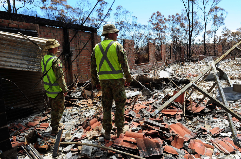 "Australian Army Sappers, Rick Pepper (left) and Pete Monkley from the 17th Construction Squadron, inspect a ruined home prior to undertaking a ""Make Safe"" task in the fire affected area of Yellow Rock in the Blue Mountains, NSW. *** Local Caption *** The Australian Defence Force has stood up an Army Engineer Remediation Force (ERF) to assist the Blue Mountains community in its recovery from the recent bush fires in the area. Comprising Army Reserve members from the 5th Brigade and Australian Regular Army members from the 6th Brigade, the ERF will assess and 'make safe' properties and infrastructure damaged in the fires. This includes removing structural and environmental hazards. The ERF, which will include approximately 90 personnel, will be drawn from Army's 5th Combat Engineer Regiment,17th Construction Squadron, 21st Construction Regiment and include equipment such as dump trucks, bulldozers, excavators, skid-steer and front end loaders, as well as teams of chain saw operators."
