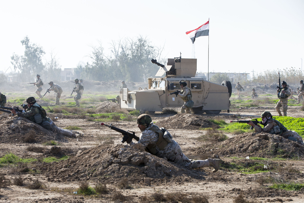 Iraqi Army soldiers assault forward during a battalion clearance training scenario at the Taji Military Complex, Iraq. Australian and New Zealand forces are assisting the Iraqi Army to enhance the ability of Iraqi soldiers to combat Daesh. *** Local Caption *** The Iraqi Army's 1st Battalion from the 71st Brigade has conducted a large culminating activity at the end of their initial training package run by Australian and New Zealand Army trainers from Task Group Taji 2. The 1st Battalion used mortar support, armoured vehicles, engineer capabilities and urban fighting skills to clear a large open area before assaulting into an urban village. 71st Brigade will now move onto an advanced training package. The Iraqi Security Forces continue to be trained by Task Group Taji personnel from Australia and New Zealand at the Taji Military Complex in Iraq as part of the broader international Building Partner Capacity (BPC) mission. The training includes weapon handling, building clearances and obstacle breaching techniques; as well as training in the Tactics, Techniques and Procedures for squad through to company-level operations to use in their fight against Daesh. Task Group Taji's BPC contribution is part of Australia's broader Defence contribution to Iraq, codenamed Operation OKRA, which includes a Special Operations Task Group and an Air Task Group.