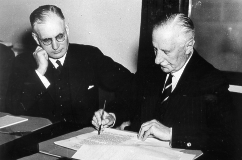 Governer General of Australia Lord Gowrie signing the declaration of war against Japan with Prime Minister John Curtin looking on.